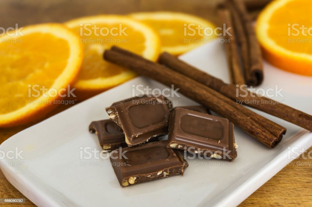 Pieces of milk chocolate with crushed, roasted almonds, cinnamon sticks and fresh orange slices in defocus. stock photo