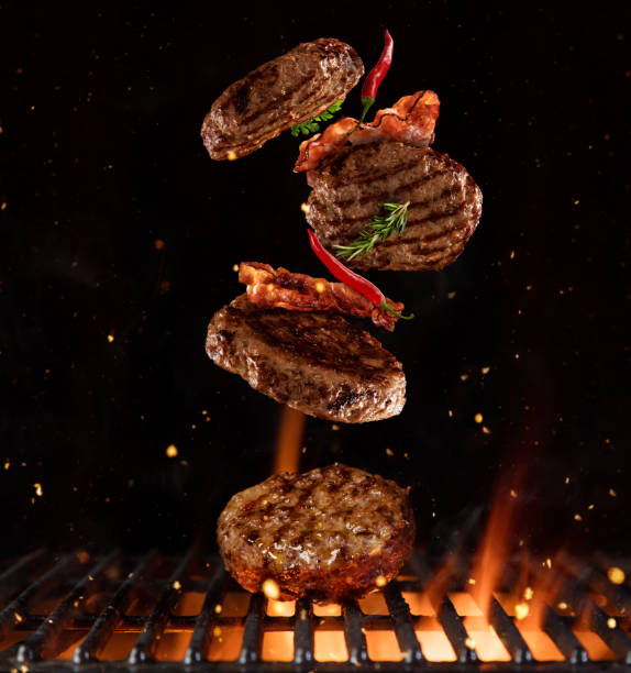 Pieces of minced meal for hamburgers flying above grill stock photo