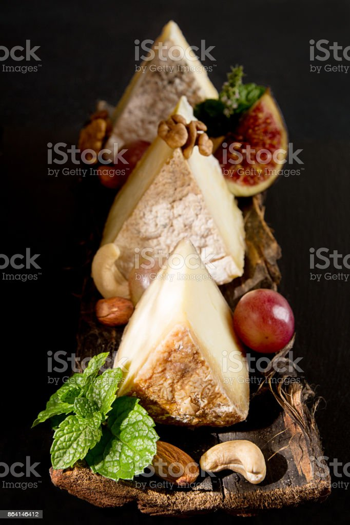Pieces of moldy cheese with grape, mint, figs, almonds, cashews on bark on black background. Food styling composition with dried cheese. royalty-free stock photo