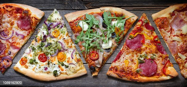 istock Pieces of pizza of different various types on old retro boards banner concept 1059162920