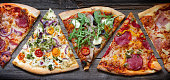Pieces of pizza of different various types on old retro boards banner concept closeup