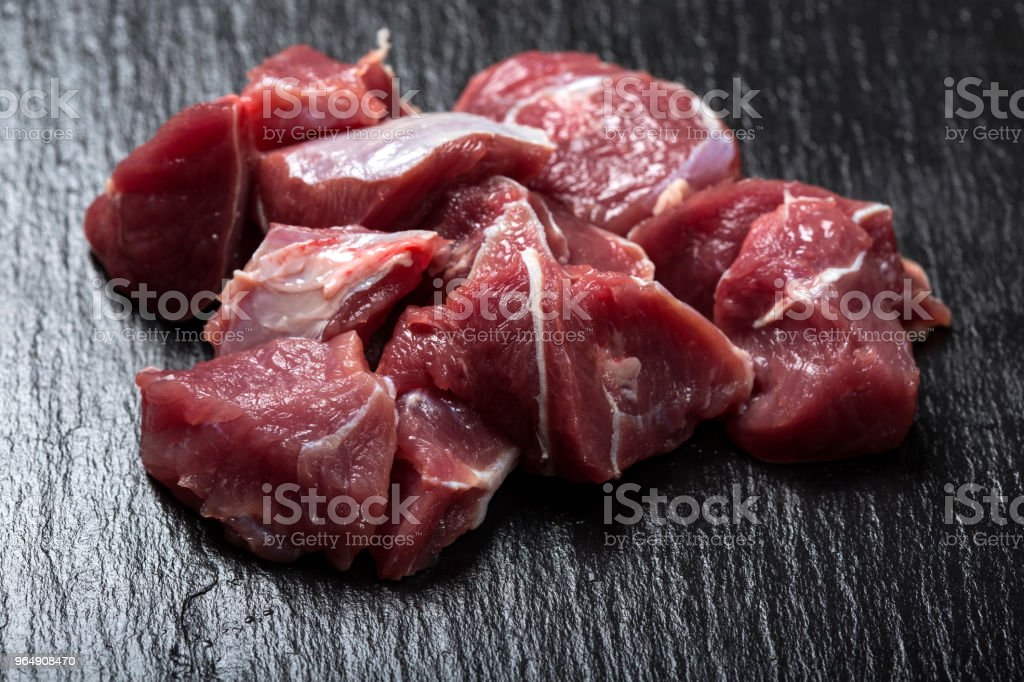 Pieces of raw beef meat on a dark slate royalty-free stock photo