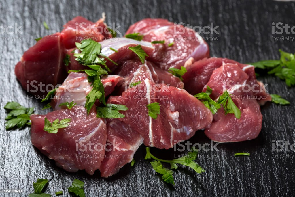 Pieces of raw beef meat on a dark slate with green herbs royalty-free stock photo