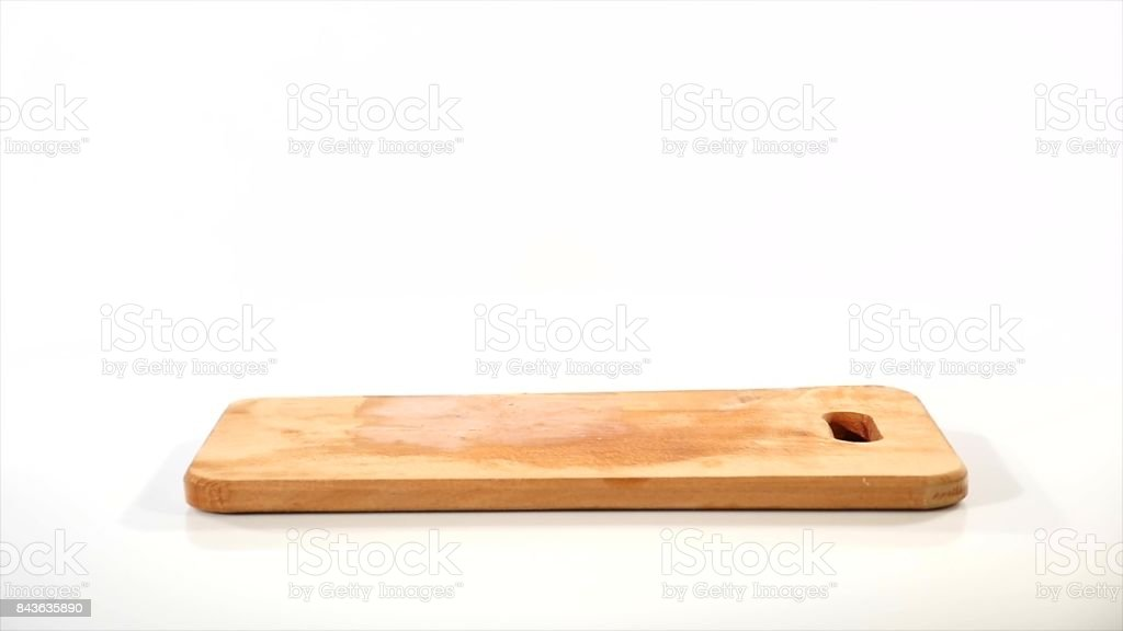 2 pieces of raw chicken fillet falls on a wooden board, than taken from a wooden plank by hand, slow motion stock photo