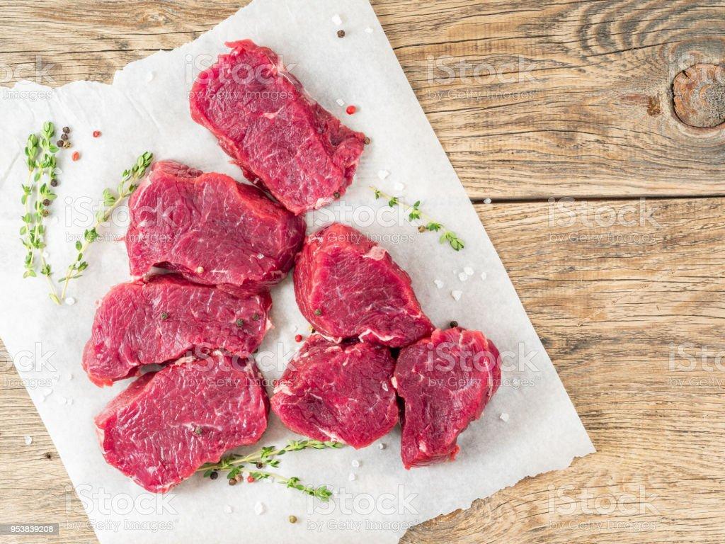 Stücke von rohem Fleisch. Rohes Rindfleisch mit Gewürzen und Thymian auf weißes Pergamentpapier auf Holz rau rustikalen Hintergrund, Ansicht von oben, Nahaufnahme, Raum zu kopieren. – Foto
