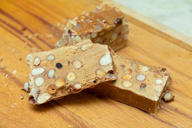 bitar av sorbet med jordnötter, orientaliska sötsaker på en trä köks bräda närbild - peanutbutter bildbanksfoton och bilder
