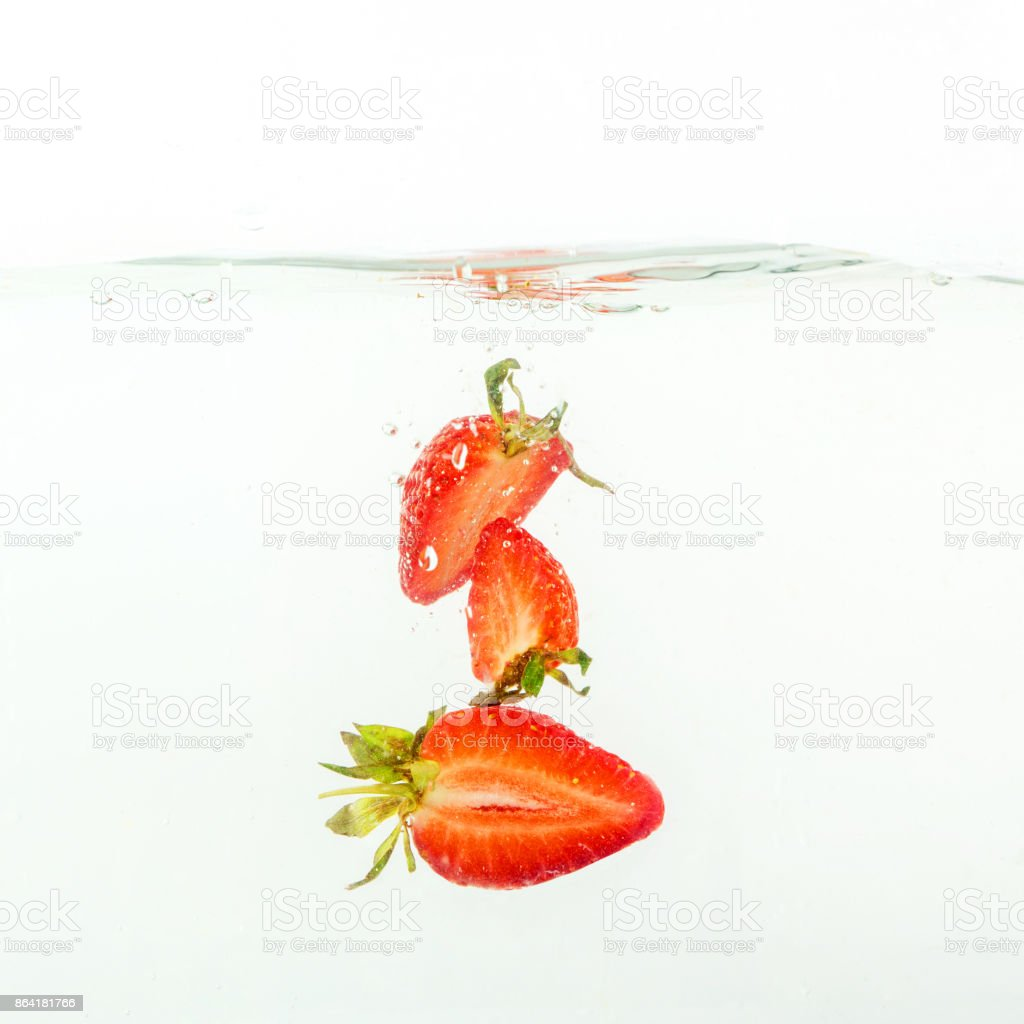 pieces of strawberries falling in water, splashes on white background, close-up royalty-free stock photo