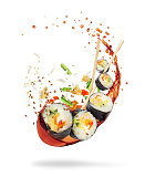 Pieces of sushi with splashes of soy sauce, isolated on white background