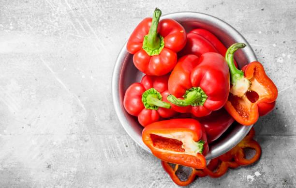 pieces of sweet pepper and whole red peppers in the bowl. - papryka słodka zdjęcia i obrazy z banku zdjęć