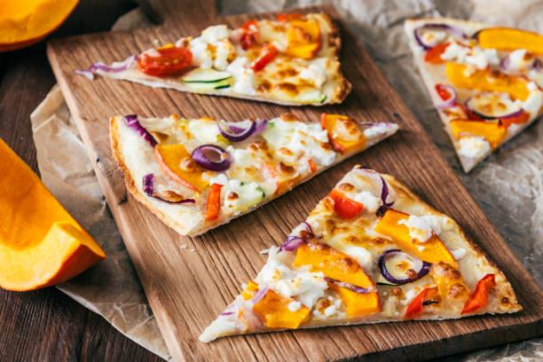 кусочки тарте фламбе с тыквой, красным луком и сыром на деревянной доске - pumpkin pie стоковые фото и изображения