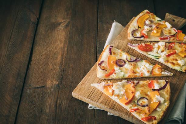 кусочки тарте фламбе с тыквой, красным луком и сыром на деревенском деревянном столе с копировальной площадью - pumpkin pie стоковые фото и изображения