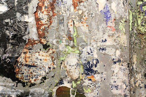483453475istockphoto Pieces of torn paper peeling off wall used as billboard 1177514850