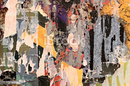 483453475istockphoto Pieces of torn paper peeling off wall used as billboard 1177515555