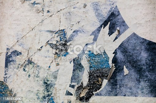 483453475istockphoto Pieces of torn paper peeling off wall used as billboard 1185930390