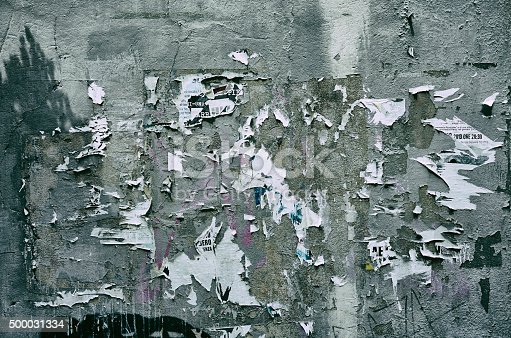 istock Pieces of torn paper peeling off wall used as billboard 500031334