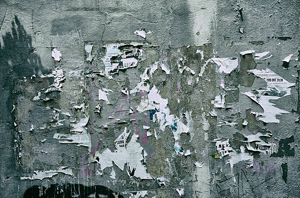 Pieces of torn paper peeling off wall used as billboard stock photo