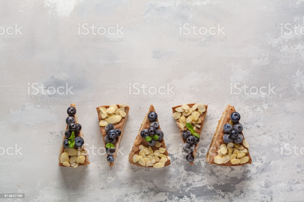 Pieces of vegan raw chocolate cheesecake with blueberries and almonds. Healthy vegan food concept, food background, copy space, top view. stock photo