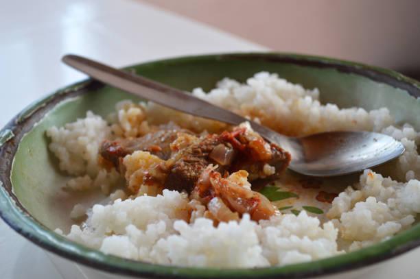Pieds de porc sauce avec du riz Les restes d'un pieds de porc en sauce avec du riz dans une assiette en fonte. riz stock pictures, royalty-free photos & images