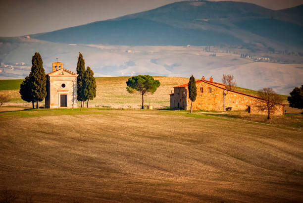 Pienza: Chapel of the Madonna di Vitaleta. Siena, Tuscany, Italy. Chapel of the Madonna di Vitaleta: the sublime in the heart of the Val d'Orcia. There are places that cannot be replicated anywhere else. As unique as the great wines. Like the masterpieces of art. Like beauty in its highest form. One of these places is the Chapel of the Madonna di Vitaleta, between San Quirico d'Orcia and Pienza. pienza stock pictures, royalty-free photos & images