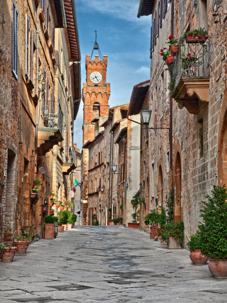 Pienza, Siena, Tuscany, Italy: the picturesque main street of the city Pienza, Siena, Tuscany, Italy: the picturesque main street of the city with the ancient buildings and the clock tower on background pienza stock pictures, royalty-free photos & images
