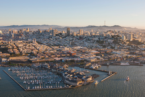 An aerial photo of the Pier 39 and Pier 41 area of San Francisco with North Beach, Little Italy, and Nob Hill neighborhoods.  Also visible is Sutro Tower on the horizon.