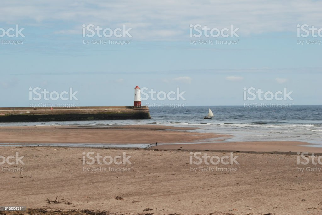 Pier and beach with old sailing yacht at Berwick-upon-Tweed stock photo