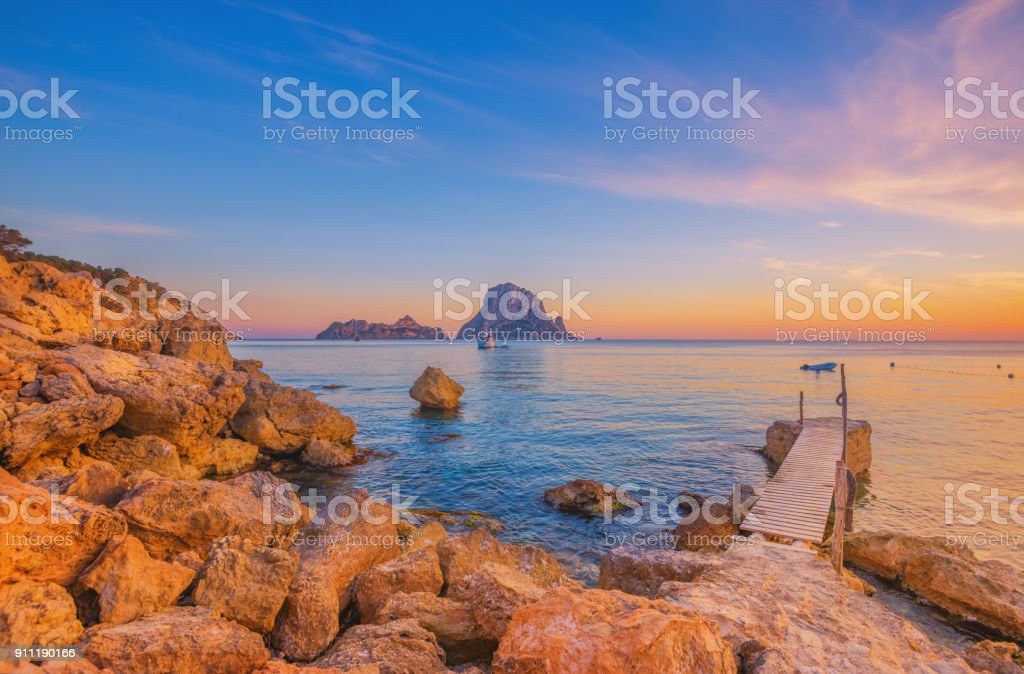 Pier and beautiful landscape at Cala d´Hort on Ibiza Pier and beautiful landscape at Cala d´Hort on Ibiza at dusk Balearic Islands Stock Photo