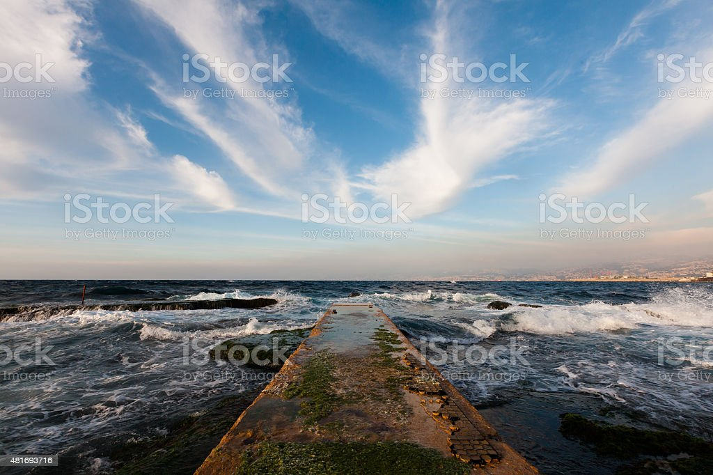 Pier and blue sky with long white clouds stock photo
