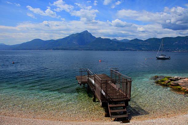 pier am lake garda strand und yacht-boot, italien - ferienhaus am gardasee stock-fotos und bilder