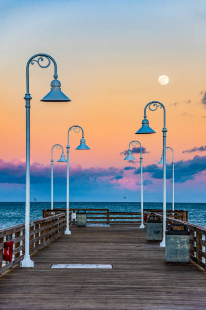 pier at sunset in daytona beach, florida - daytona 500 stock photos and pictures