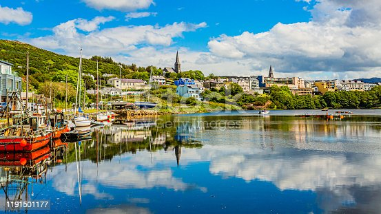 Pier at the port of Clifden at high tide, boats anchored with mirror reflection in the water, sunny spring day with a blue sky and abundant white clouds in Clifden, Ireland