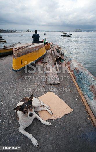 Rio de Janeiro, Brazil - August 17 2013: Boats and fishermen in front of rio de janeiro, next to the ferry terminal and Niteroi bridge