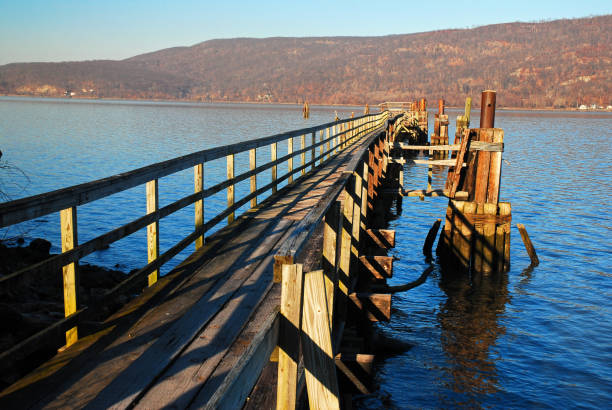 A pier extends into the river stock photo