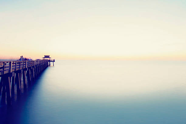 Pier in Pastel Colors A horizontal slow shutter image of a wooden pier and a calm ocean. naples florida stock pictures, royalty-free photos & images