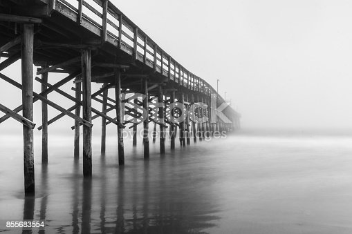 A black and white photo of a pier in the fog