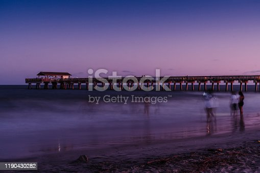 The fishing pier and Atlantic Ocean at Tybee Island in the purple light of the setting sun. Long exposure photo, unrecognizable people.