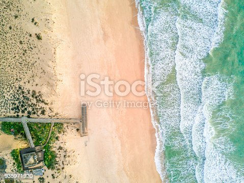 Wooden pier leading to sandy beach and waves on Atlantic Ocean in Quinta do Lago, Almancil, Algarve, Portugal