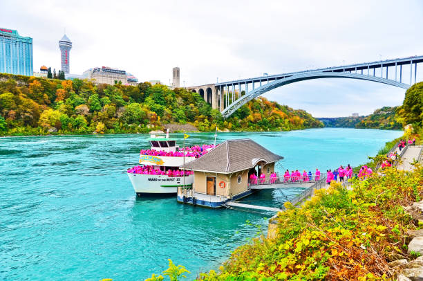 Pier of the tour boat - Maid of the Mist Niagara Falls, USA - October 13, 2013: Pier of the tour boat - Maid of the Mist with lots of tourists wearing purple raincoat in Niagara Falls on October 13, 2013. rainbow bridge ontario stock pictures, royalty-free photos & images