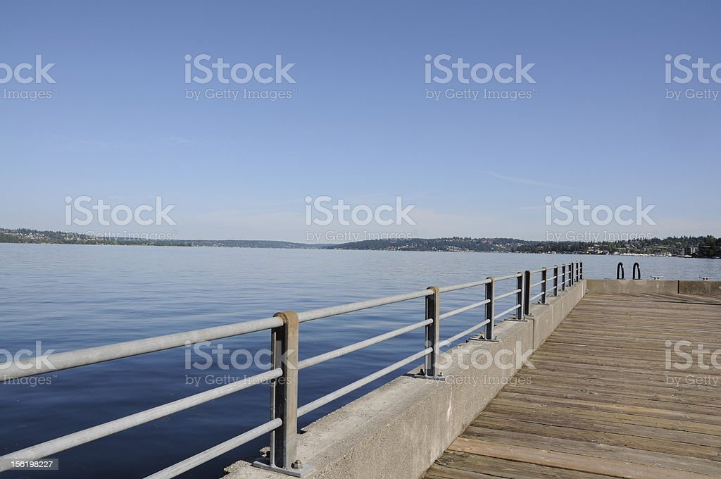 Pier on a lake with matching blue water and sky royalty-free stock photo