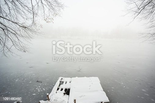 Pier on frozen winter lake in the fog