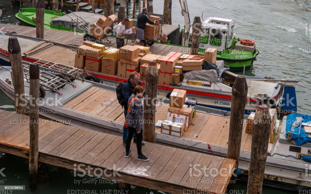 Pier on the Grand Canal. Designed for cargo ships. cargo ships. Boats and gondolas are moored. Tourists visiting the pier. stock photo