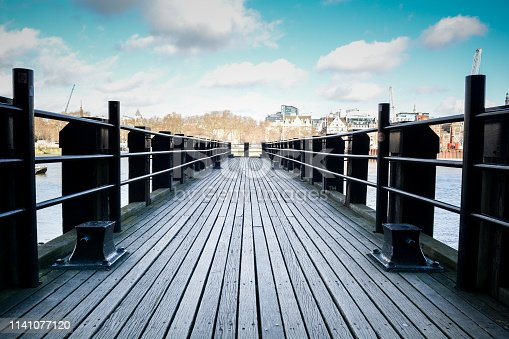 Wooden pier in a peaceful scene overlooking a city river