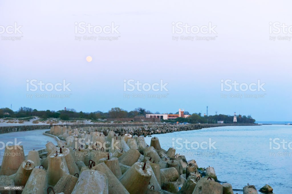 pier sea and coastal fortifications, concrete breakwaters protecting the sea shore, full moon and sea pier royalty-free stock photo