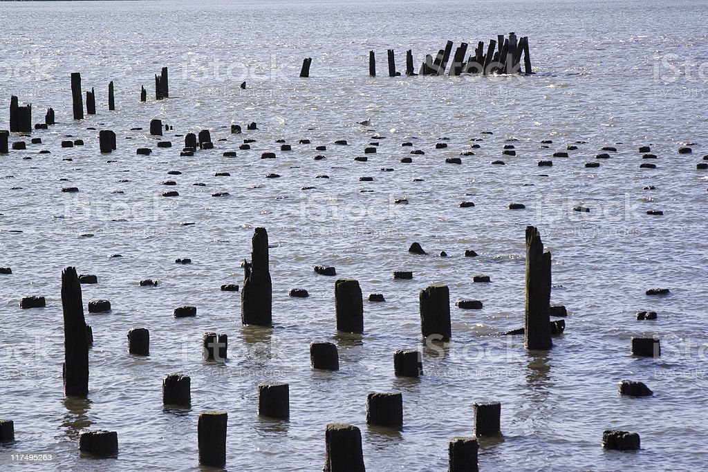 Pier stumps in the middle of the ocean stock photo