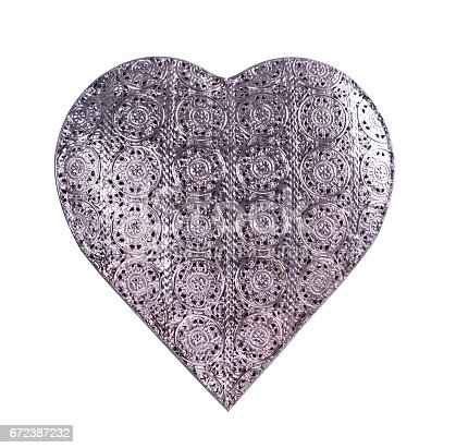 A pretty heart-shaped ornament made of silver metal isolated on a white background.