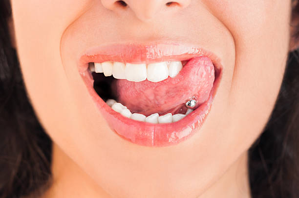 Pierced tongue licking lips stock photo