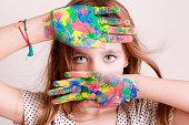 Peinture vive sur les mains d'une petite fille au regard vif