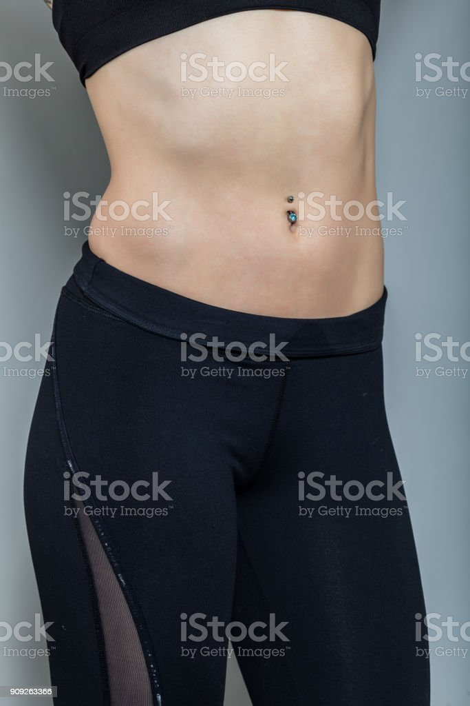 Piercing on the umbilicus. Female navel with jewelry. stock photo