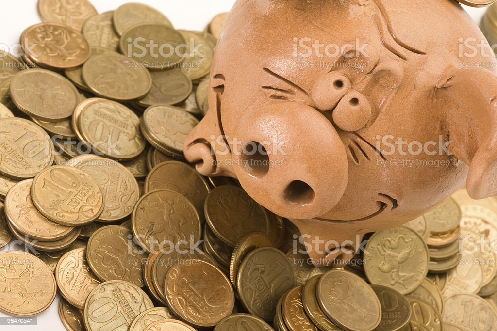 Pig bank seat on a heap of coins royalty-free stock photo