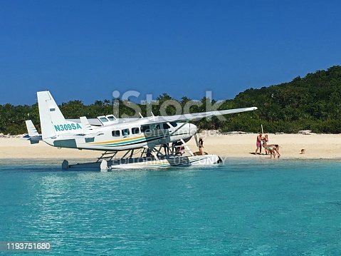 A float plane lands from Fort Lauderdale on Pig Beach on Big Major's Spot in The Bahamas to depot tourists so they can feed the pigs